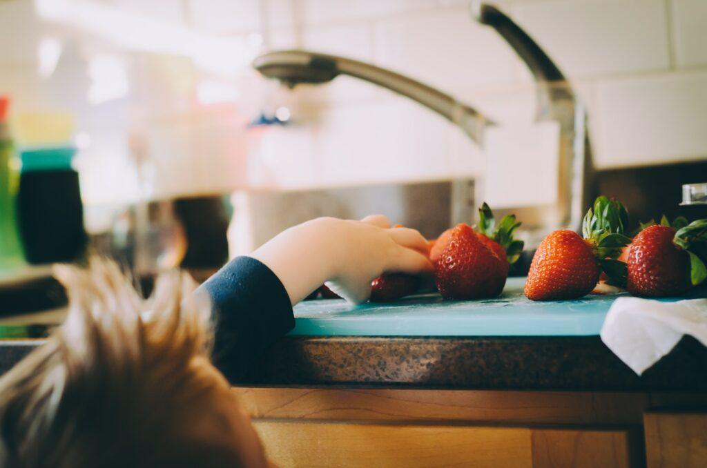 Kind greift nach Obst
